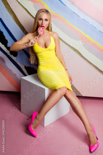 Young, cute, beautiful slim blonde woman with african braids and with lollipop i Poster