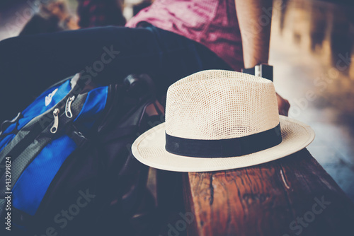 Close up of hipster traveller man siting on bench with backpack in train station waiting for go travel with the train Poster