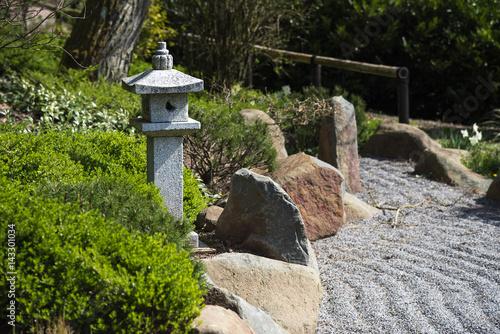 Stone lantern between evergreen plants, rocks and raked gravel, zen garden lands Poster