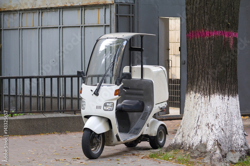 Foto op Canvas Scooter White scooter is parked on the sidewalk. Transport