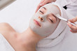 Leinwanddruck Bild - Woman gets face mask by beautician at spa