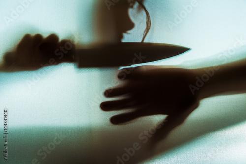 Poster der Schatten einer Frau mit einem Messer ist im Gegenlicht zu sehen