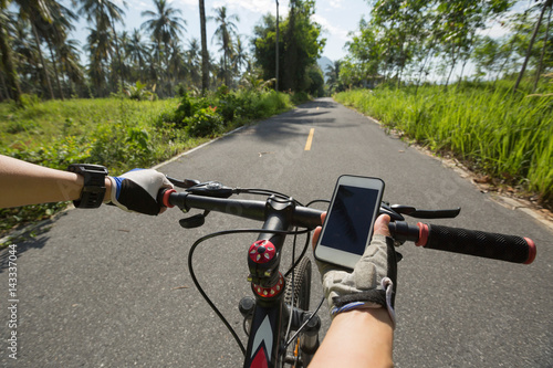 Deurstickers Fietsen cyclist hands use smartphone for navigator when riding mountain bike on forest trail