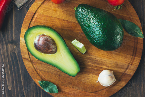 Top view of avocado standing on wooden board surrounded by vegetables.