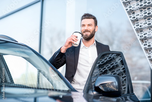 Portrait of an elegant businessman standing with coffee cup near the car Poster