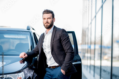 Portrait of a handsome businessman standing near the car outdoors near the moder Poster