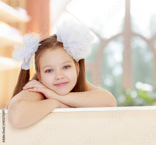 Beautiful little girl with white bows on the head