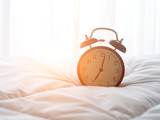 Alarm clock on bed in morning with sun light.. - 143377283