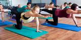 Adults having yoga class in sport club