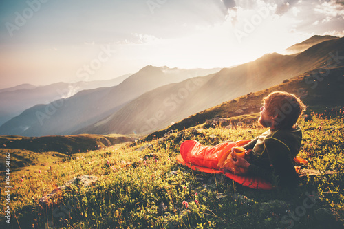Leinwanddruck Bild Man relaxing in sleeping bag enjoying sunset mountains landscape Travel Lifestyle camping concept adventure summer vacations outdoor hiking mountaineering harmony with nature