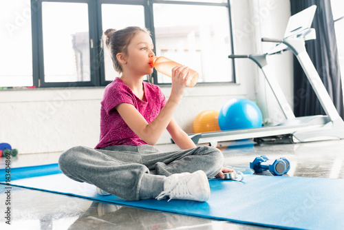 adorable girl in pink shirt sitting on yoga mat and drinking water in gym