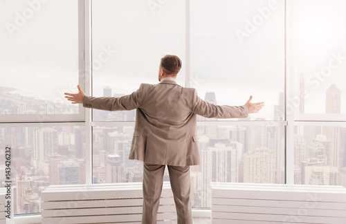 Pleasant businessman enjoying the view from his office
