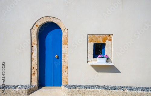 Typical cycladic house with blue door and window.