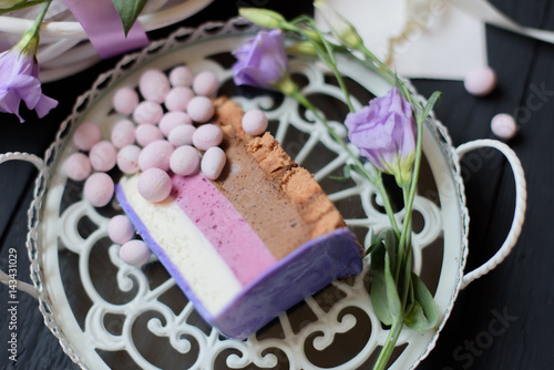 Piece of blueberry cake with flowers on black wooden background