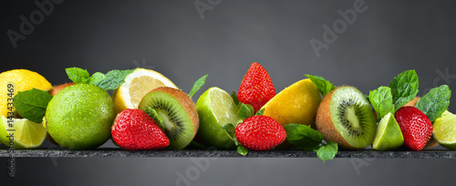 Ripe juicy fruits and peppermint with water drops