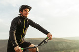Young male riding bicycle among mountains