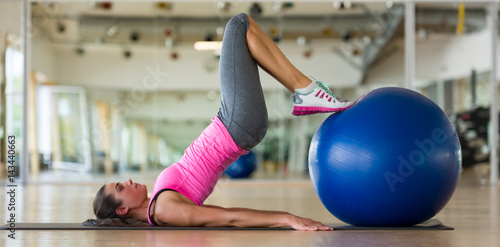 Juliste Beautiful athletic woman doing fitness exercise with ball in gym