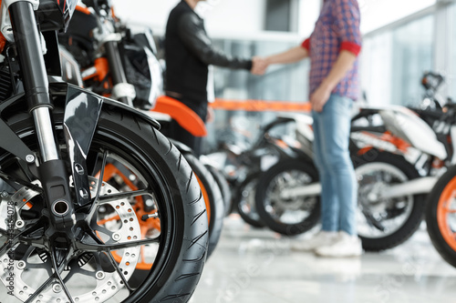 Thanks for help. Selective focus on a motorcycle wheel male customer shaking hands with motorbike salon manager on the background
