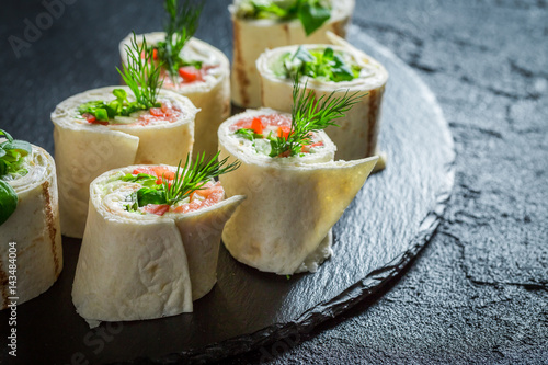 Fresh rolls with salmon, cheese and vegetables for a brunch - 143484004
