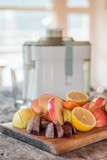 Juicer surrounded by healthy fruits and vegetables