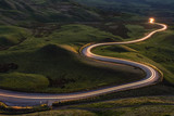 Winding curvy rural road with light trail from headlights leading through British countryside. - 143487869