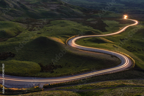 Winding curvy rural road with light trail from headlights leading through British countryside.