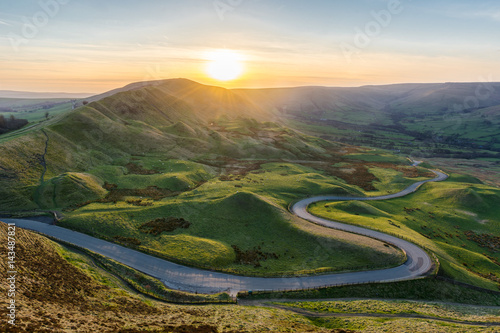 Sunset at Mam Tor in the Peak District with long winding road leading through valley