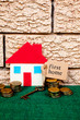 House with coins with brick background - with First Home key