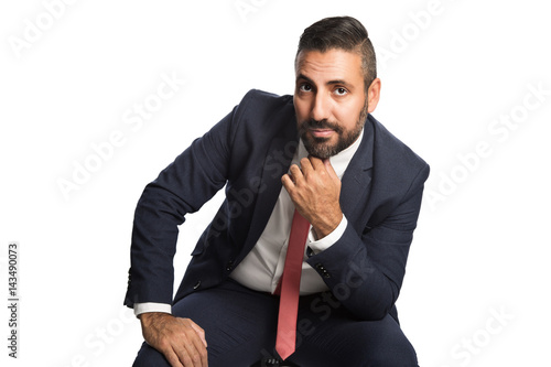 Handsome businessman in a blue suit and red tie, sitting down in front of a white background with his hand on knee Poster