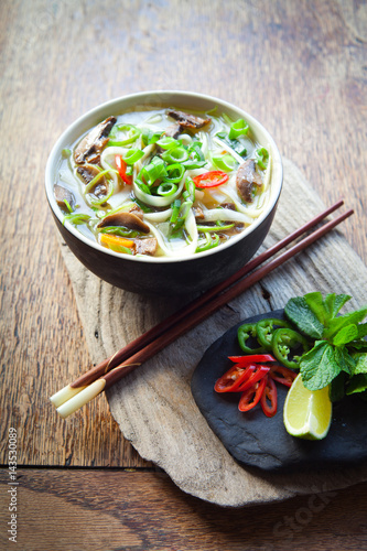 Spicy Vegetarian Rice Noodle , Vietnamese vegetable Pho Soup , Asian cuisine cooking spices: ginger, lime, chili, garlic, spring onions,lemon grass, chives, shallots, mint and shiitake mushrooms.