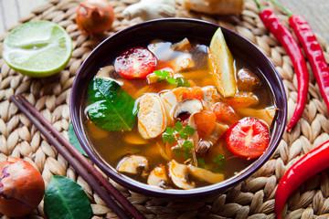Asian Vegetarian Vegan soup with tofu, lime, galangal, chili, tomato, shiitake mushrooms, basil and coriander leaves.
