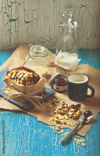 Poster cookie with peanuts and chocolate icing, blue cup of milk, glass jars and jam on
