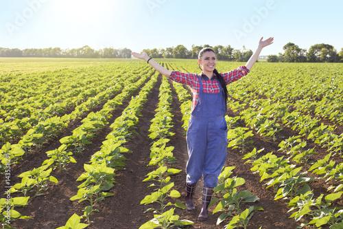 Happy farmer girl in sunflower field