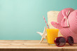 Summer holiday vacation concept with orange juice, hat and sunglasses on wooden table