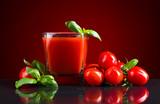 Glass of tomato juice with red small tomatoes