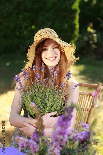 Attraktive rothaarige Frau im sommerlichen Garten mit Lavendel