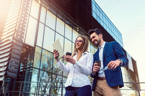 Business couple outdoors in the street taking a coffee break using digital tablet
