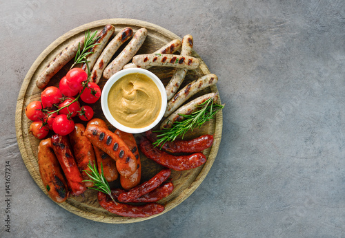 Grilled sausages on a round board - 143657234
