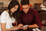 Young couple using phone at the restaurant - 143668613