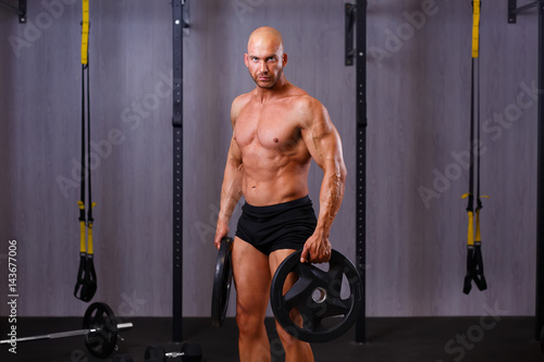 Young healthy bald ripped man with big muscles holding disk weig