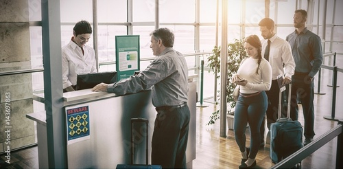 People waiting in queue at airplane counter