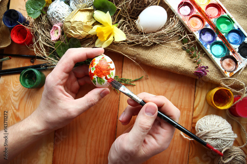 A man paints Easter eggs. Easter composition