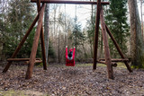 young woman in red dress using swings in spring forest