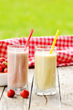 Banana and strawberry milkshake smoothie in the glass with straw
