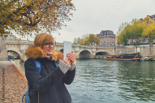 Poster Cute girl using cellphone with Seine river in the background, Paris - France