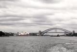 Skyline von Sydney mit Opera House und Harbour Bridge an einem bewölkten Tag.