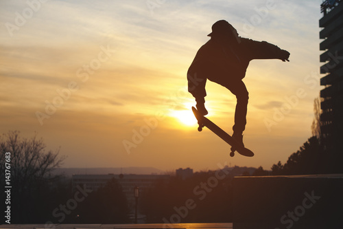 The teenager in a sweatshirt and a cap jumps with a board in the city against the backdrop of the urban sunset