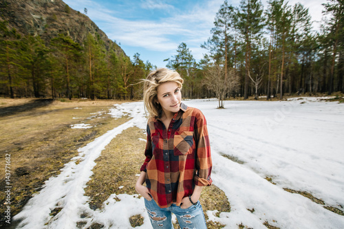 Poster blonde girl in the plaid shirt in spring forest