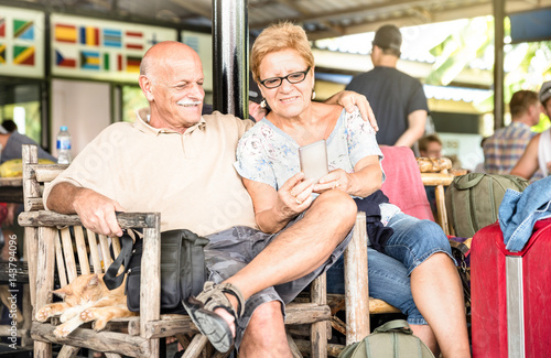 Happy senior couple sitting and using mobile smart phone with travel suitcase du Poster