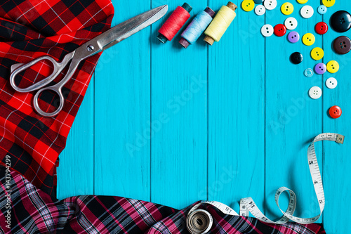 Checkered fabrics collection, measuring tape, buttons, sewing threads and tailor